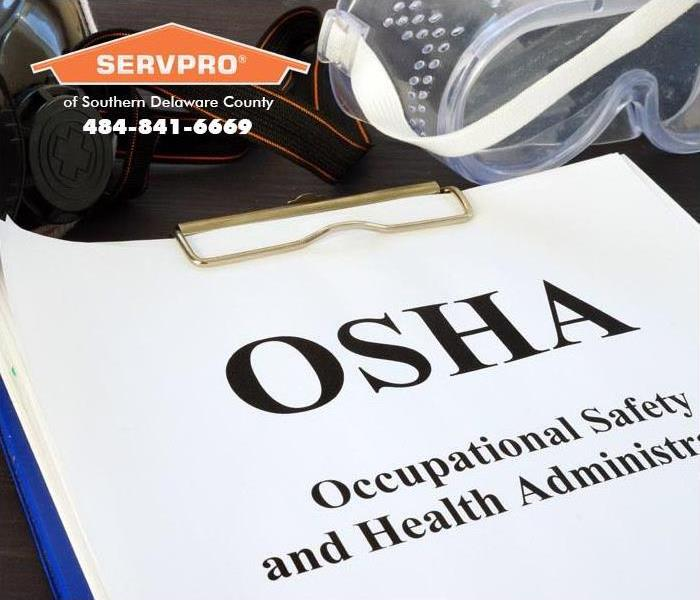 """OSHA"" Occupational Safety and Health Administration written and clipped onto a clipboard."