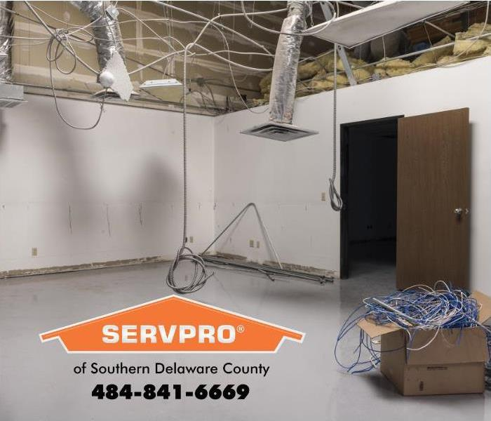 A large room inside a commercial building is shown in the process of completing electrical and structural repairs.